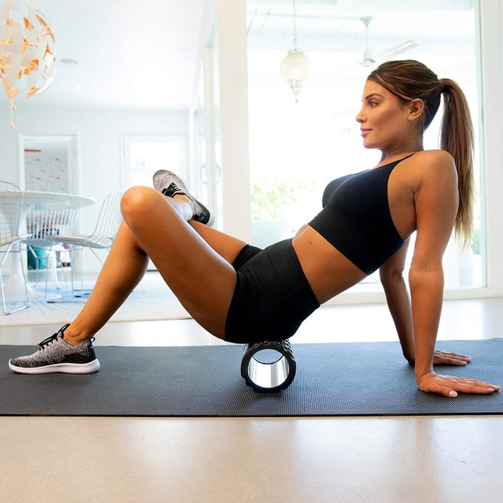 Model uses black foam roller on their quad muscles