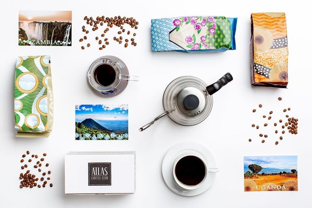 A birds eye view of the subscription box, bags of coffee, and cups of coffee spread out on table