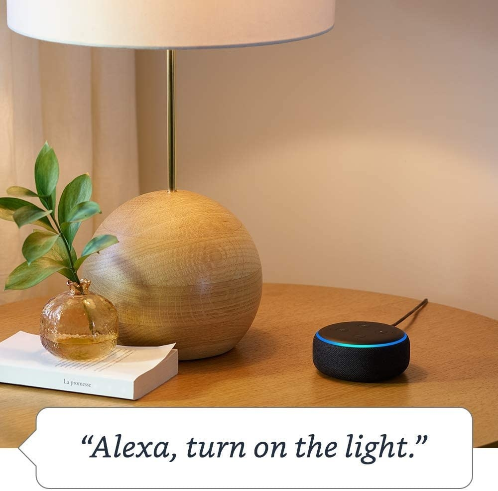 "The black Echo Dot on a table with the text ""Alexa, turn on the light"" on the image"