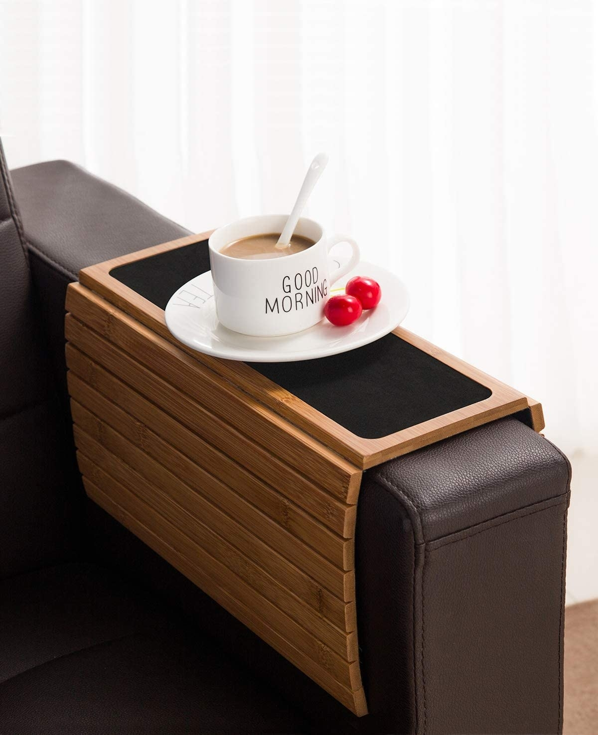 The light brown-colored wood slotted tray over the side of a couch with a black mat on the top and a coffee cup on it