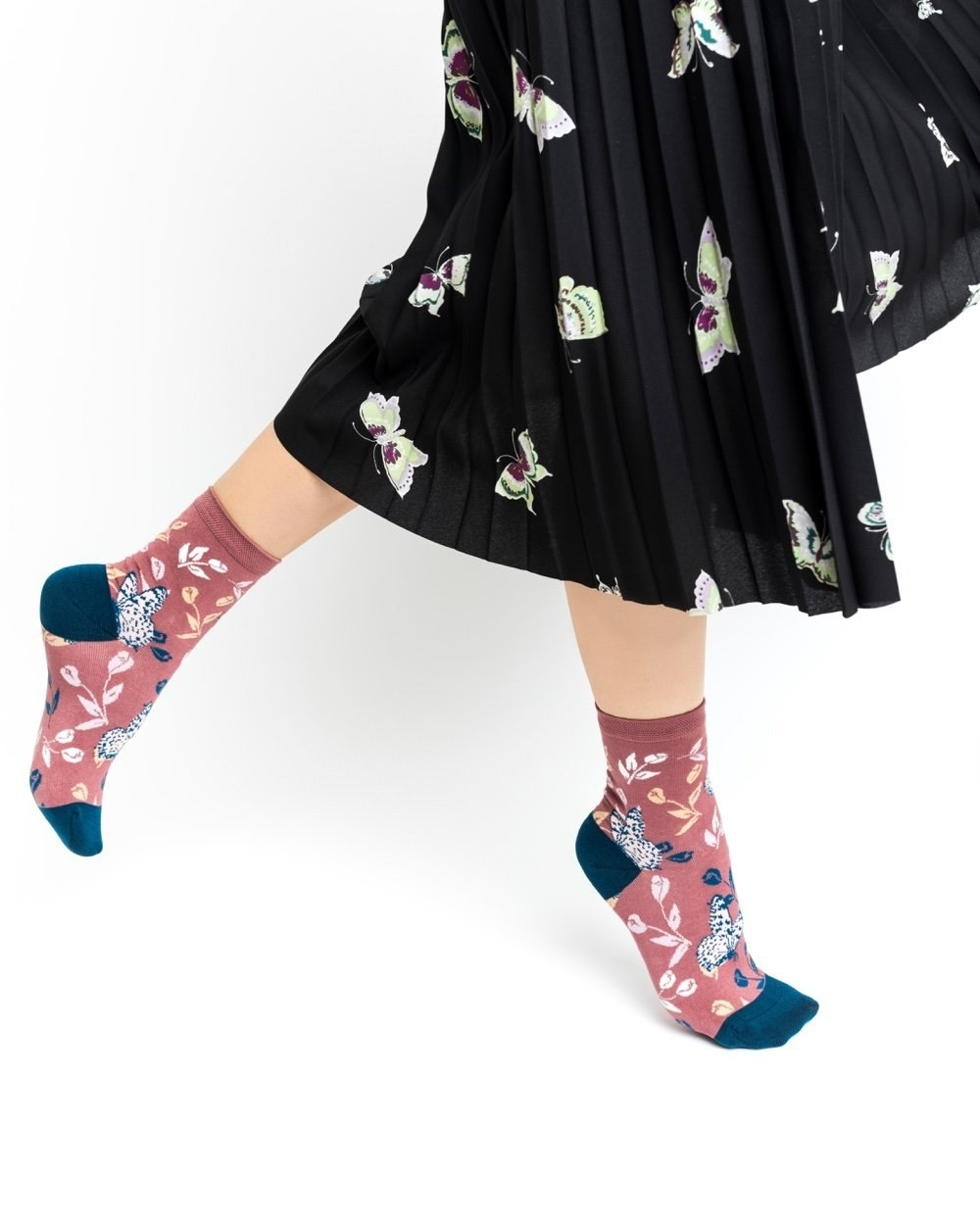 A model wearing the tossed butterfly ankle sock