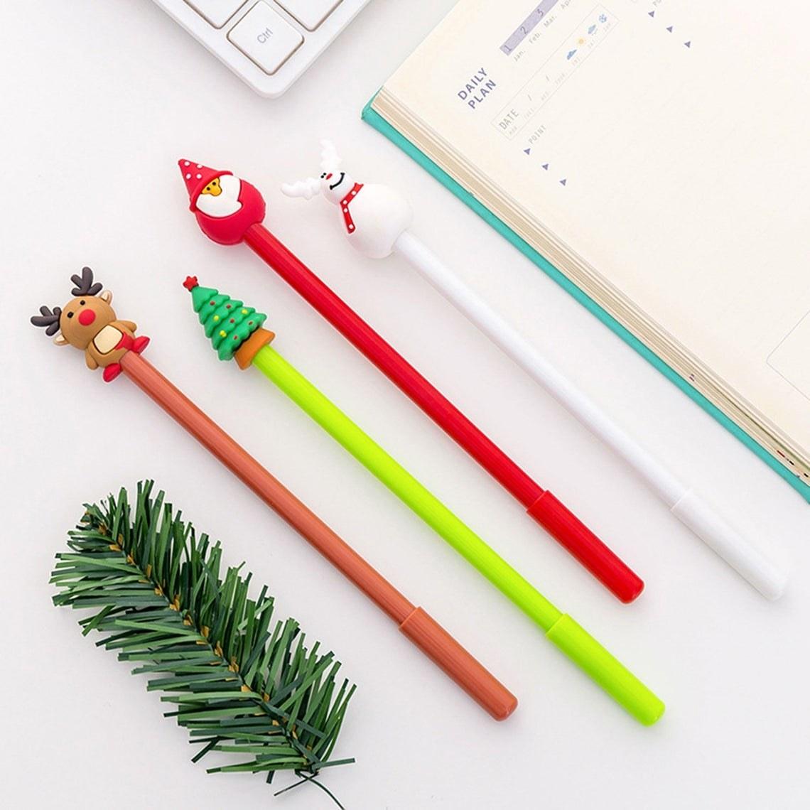 pens topped with reindeer, christmas tree, santa, and snow-deer