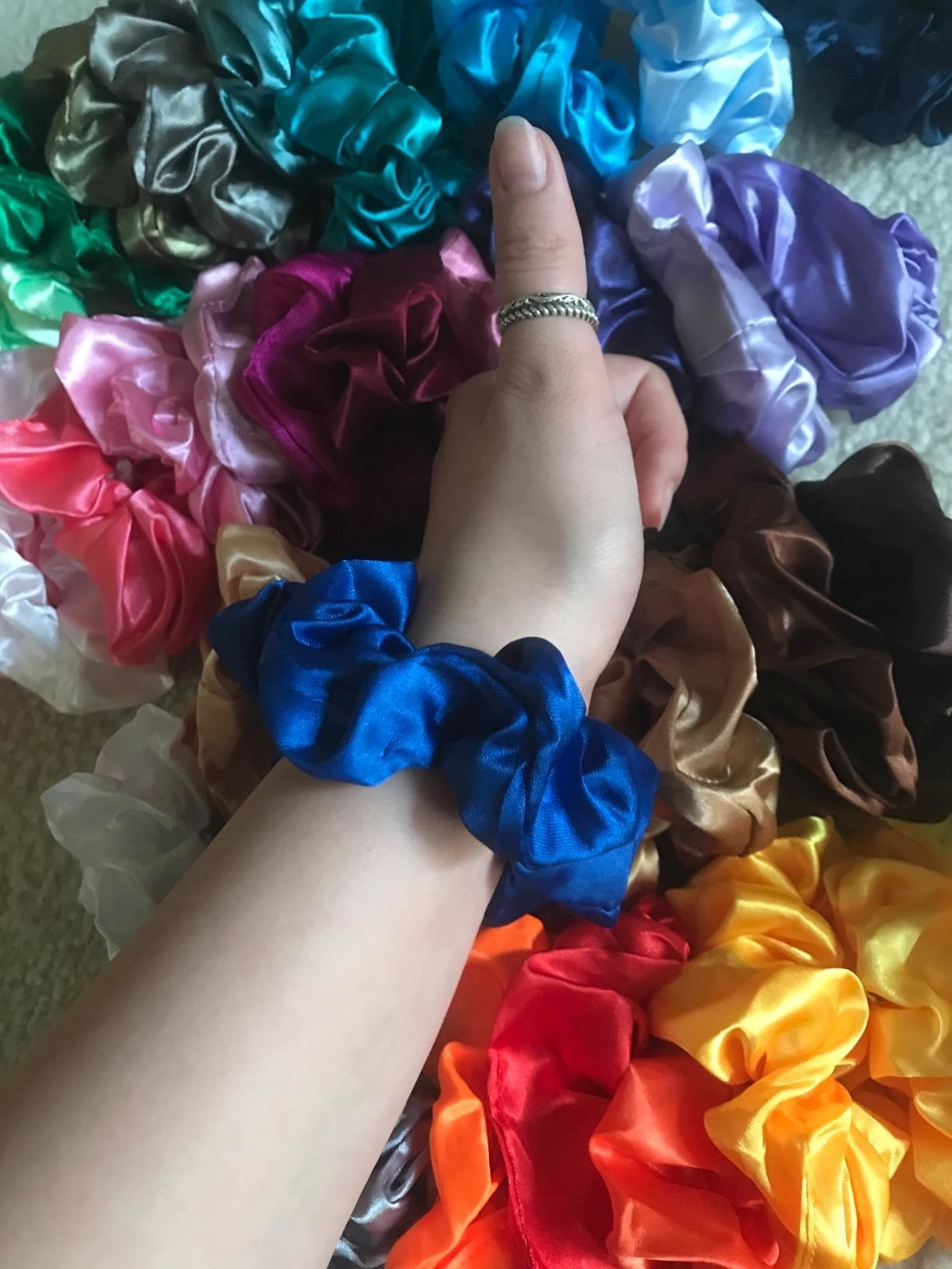 reviewer wears a scrunchie and gives thumbs up to pile of scrunchies