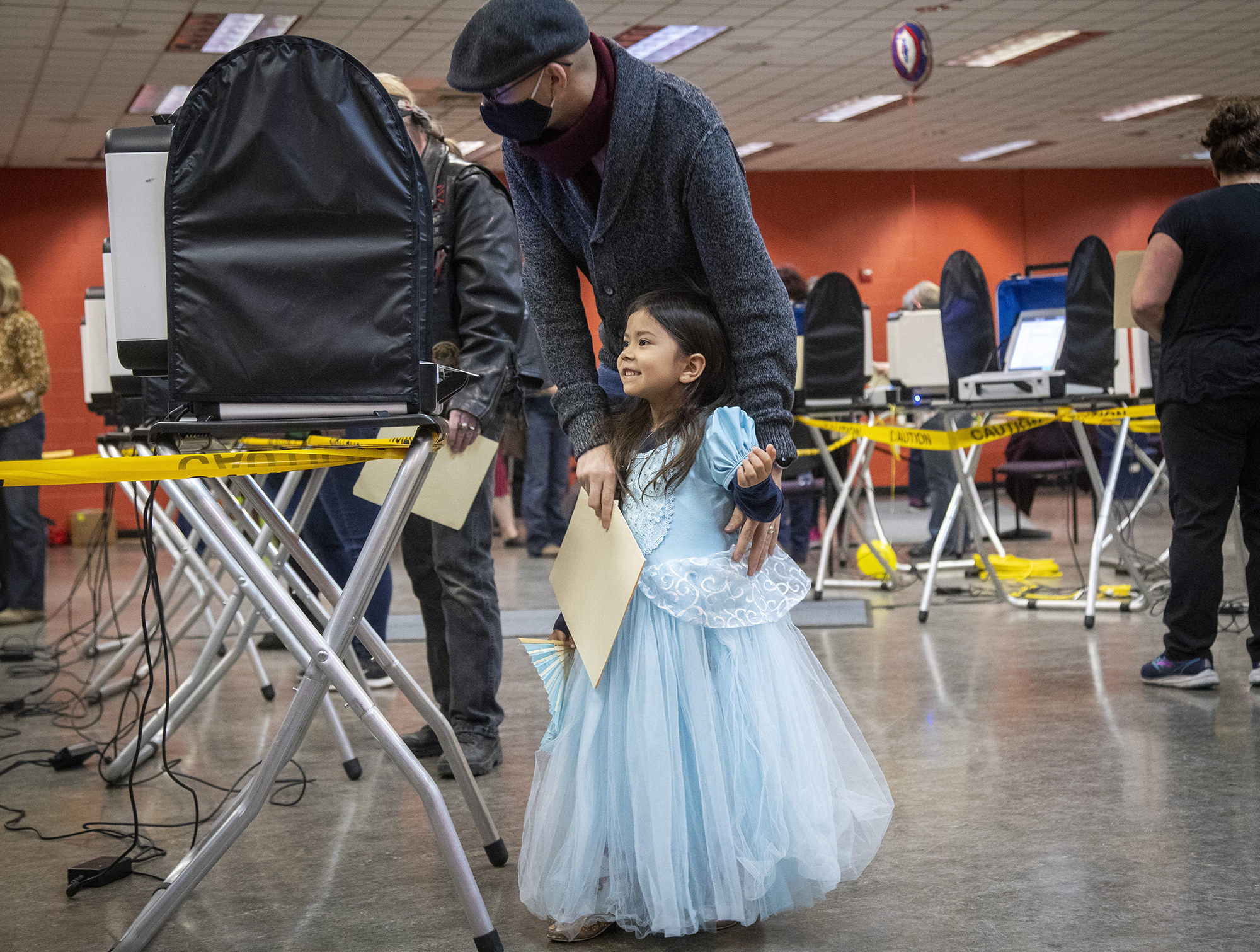 A young girl in a princess costume with her dad at the polls