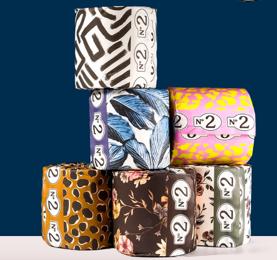 Several stacked toilet paper rolls wrapped in different bold patterns of tissue paper