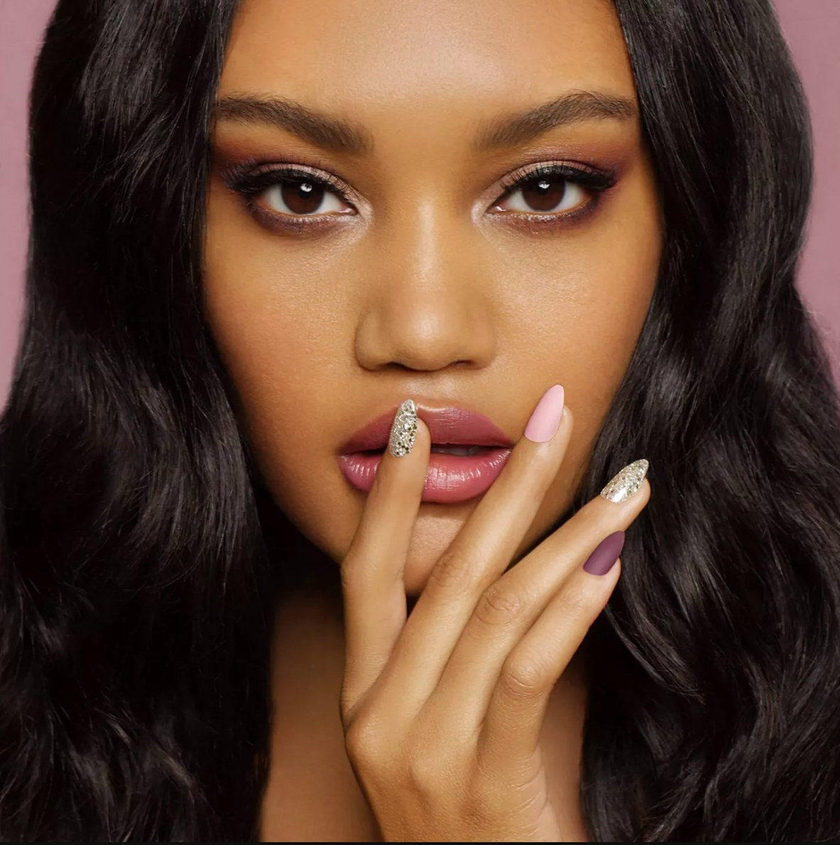 Model wearing the fake nails in several metallic and pink shades