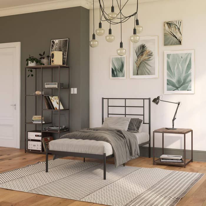 The bed frame, which is metal, with lots of space beneath, no box spring or foundation, and a headboard of rectangular shapes