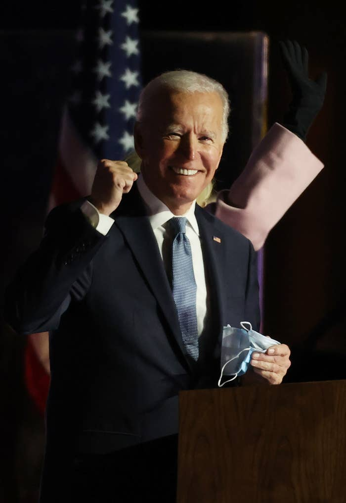 Biden pumps his fist while standing a podium