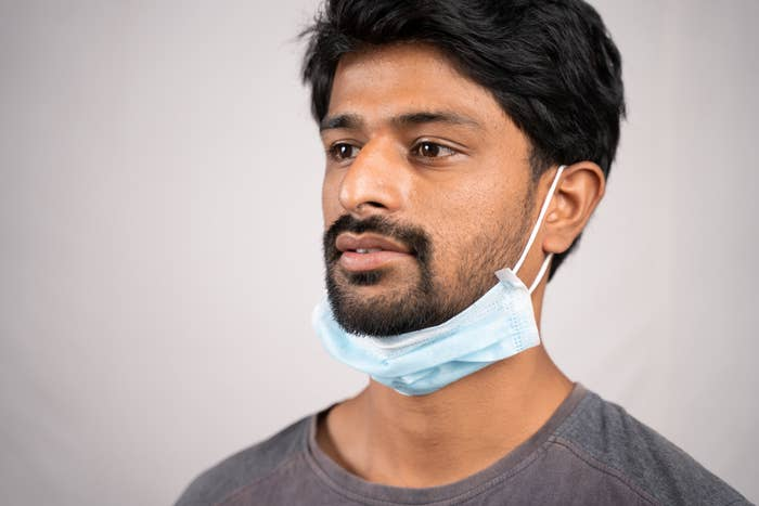 concept showing of improper way of using face masks during coronavirus or covid-19 crisis - young man wearing medical at neck on isolated background
