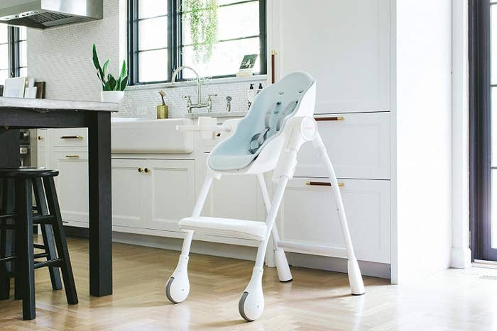 White and light blue high chair with two gray wheels