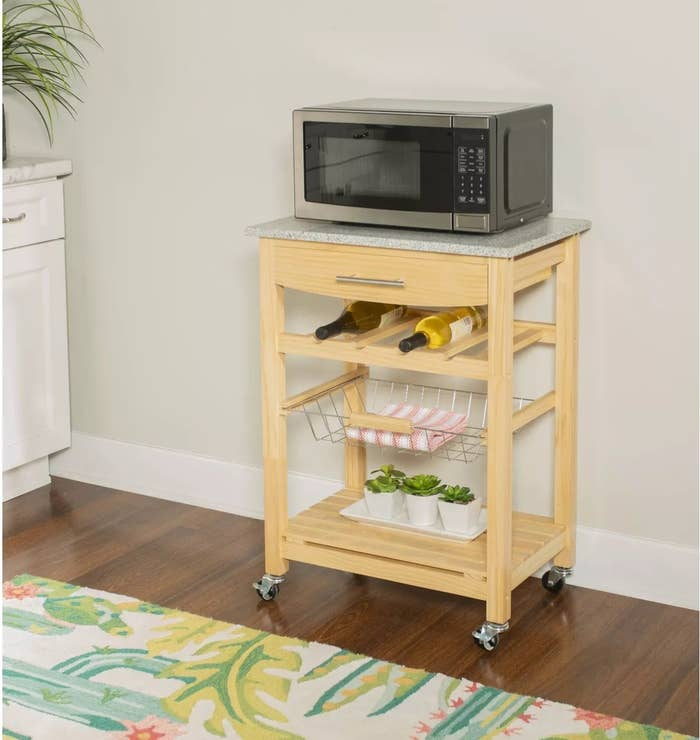 Wooden kitchen island on wheels with gray marble top