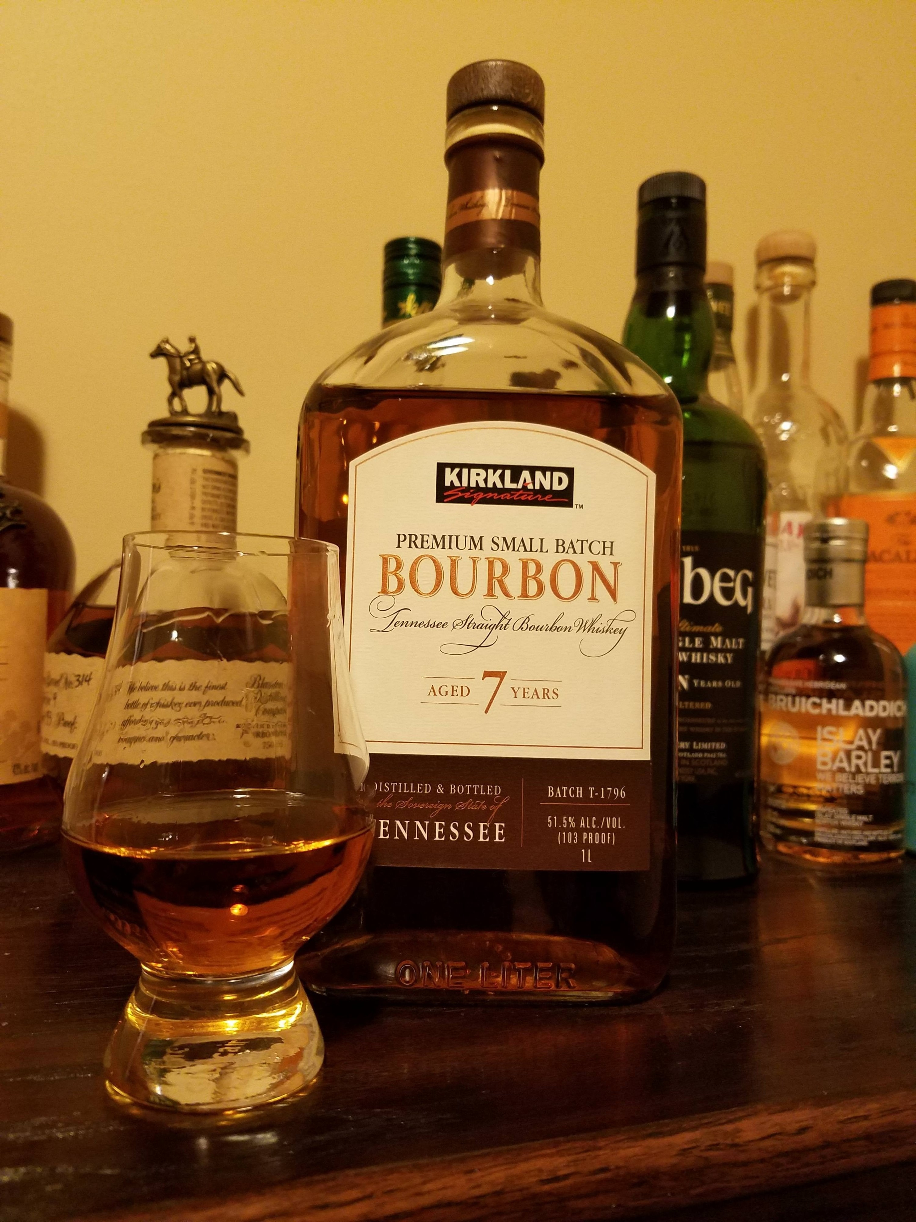 A bottle of Kirkland small batch 7 year aged whiskey and a glass of it.