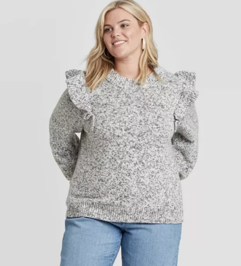 model wears the grey sweater with ruffled shoulders