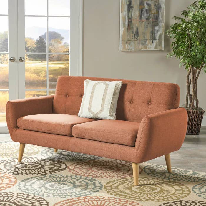The salmon-colored couch with wooden legs