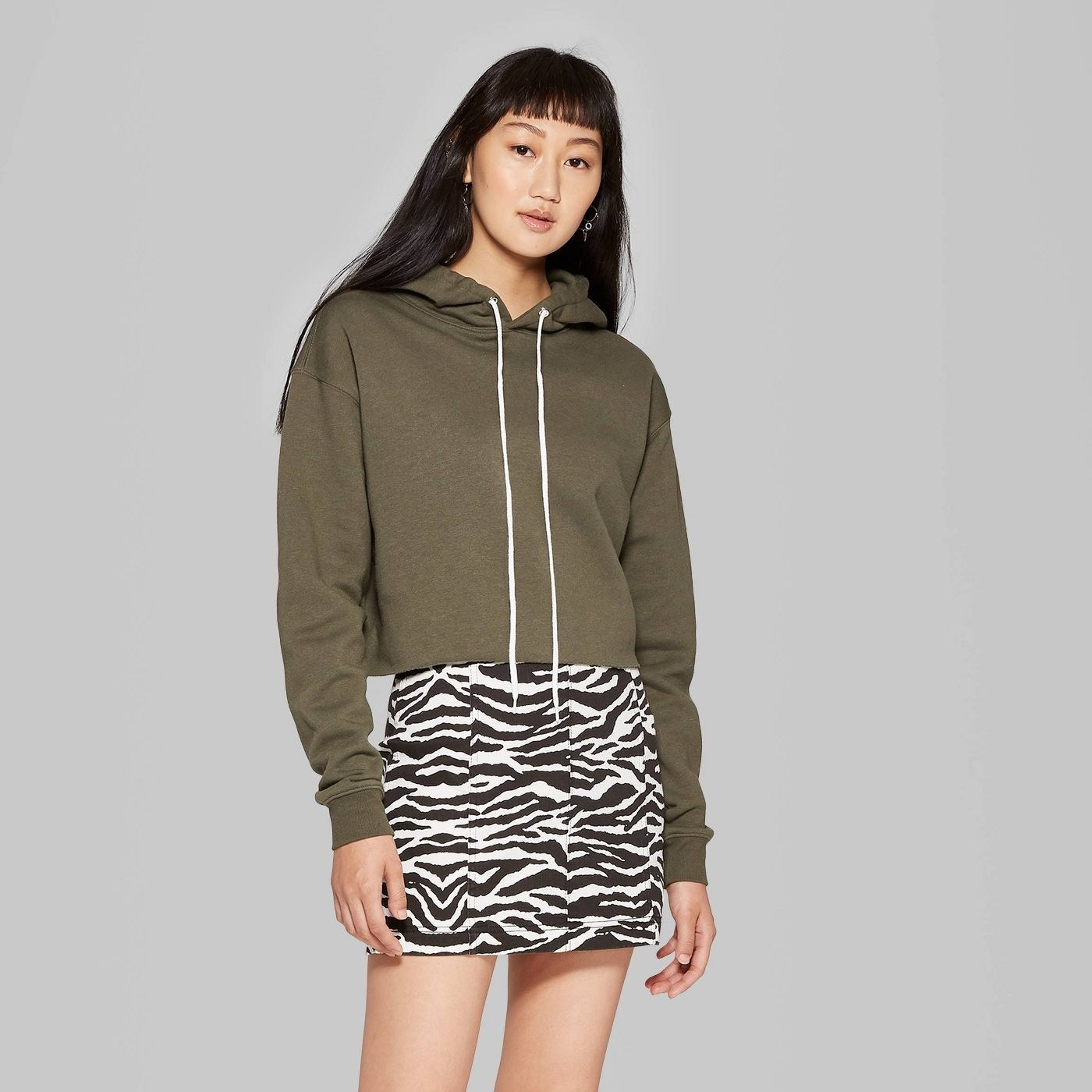 Model in green cropped hoodie and zebra print skirt