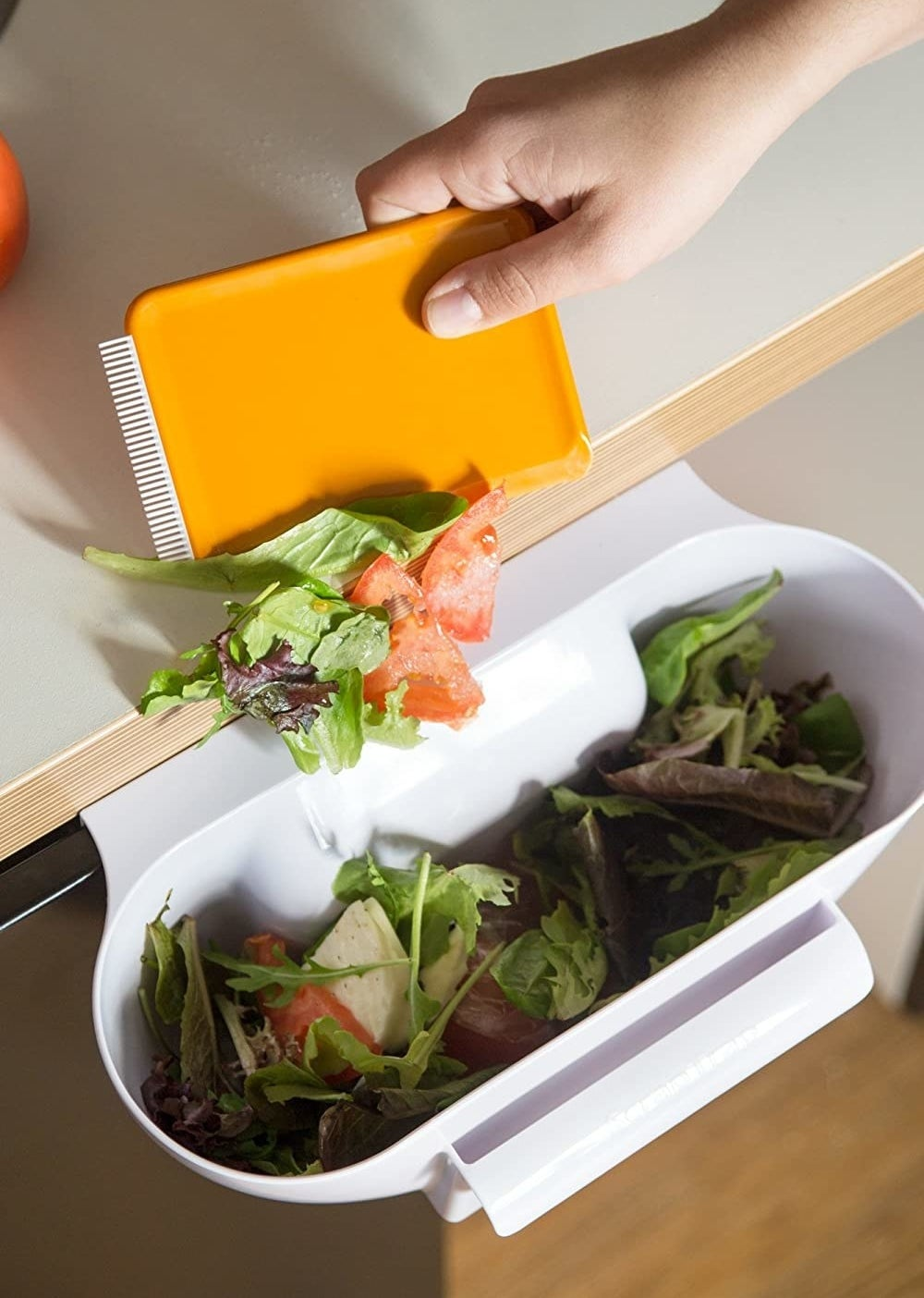 A person scoops kitchen scraps off the counter and into the cabinet-mounted trap