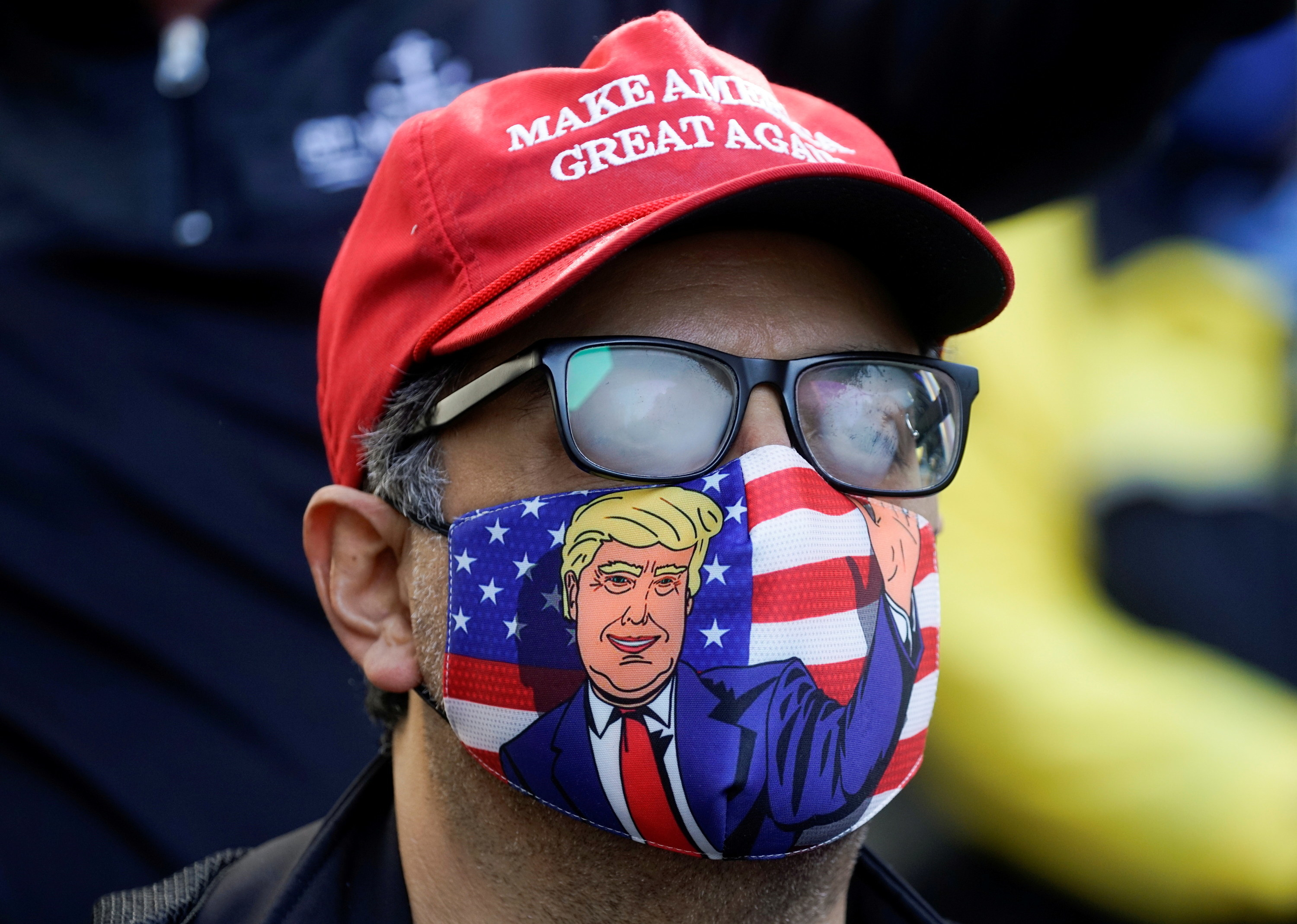 A man in a trump face mask
