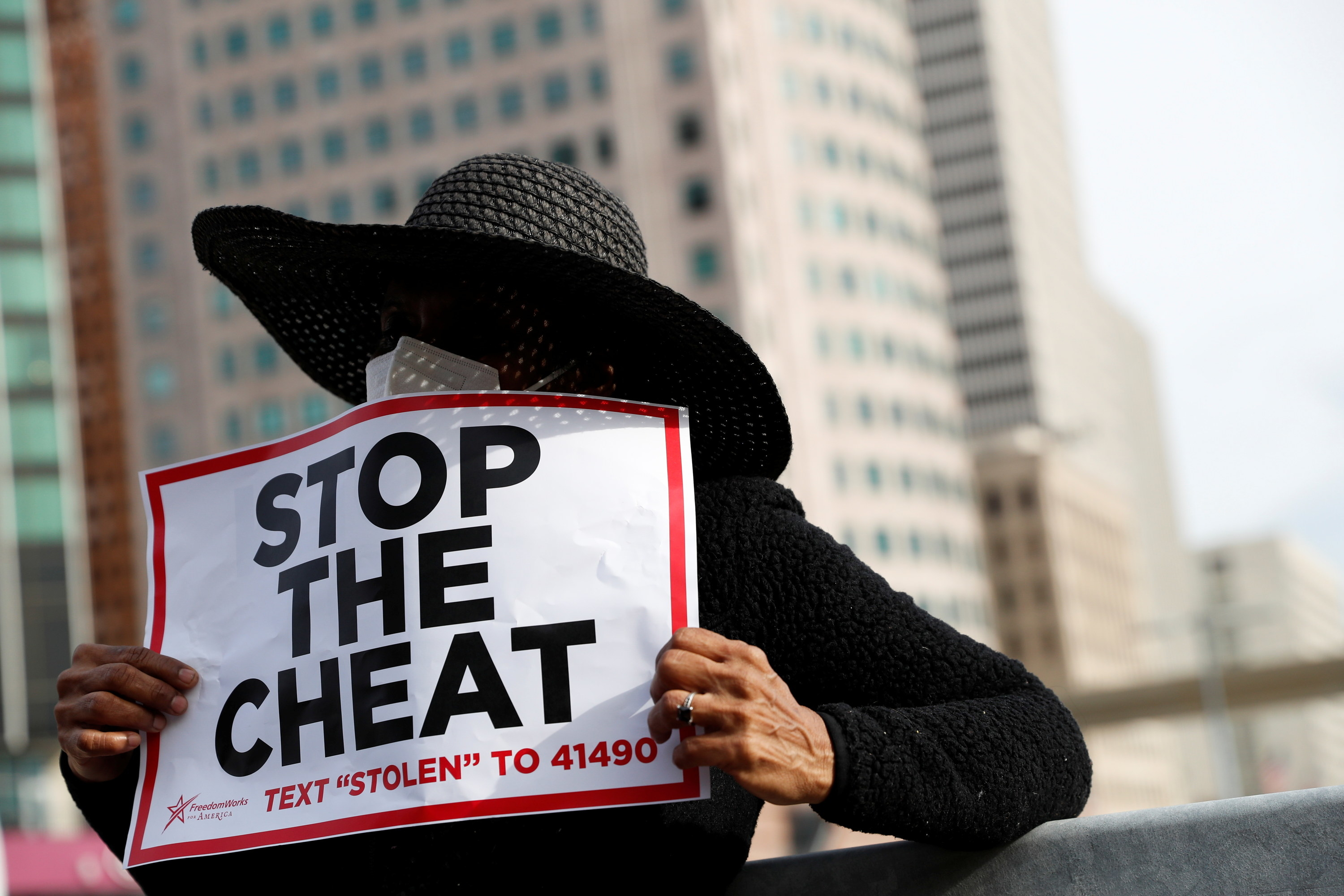 A person with a stop the cheat sign