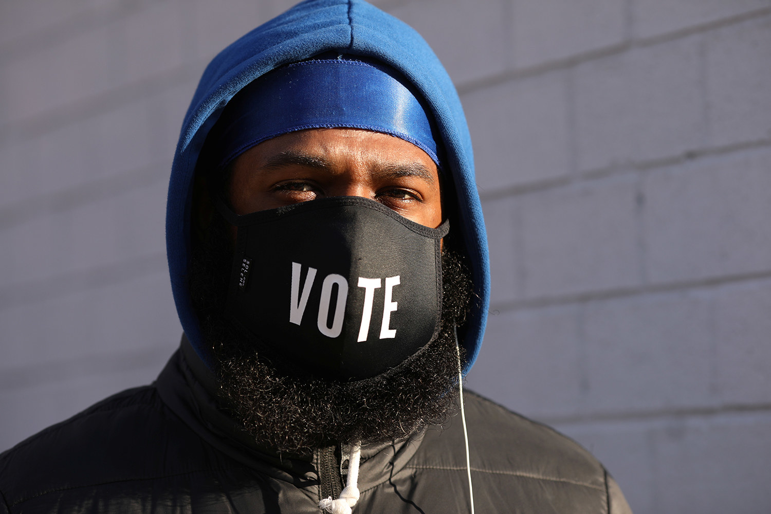 """A Black man in a blue hoodie wears a face mask that says """"Vote"""""""