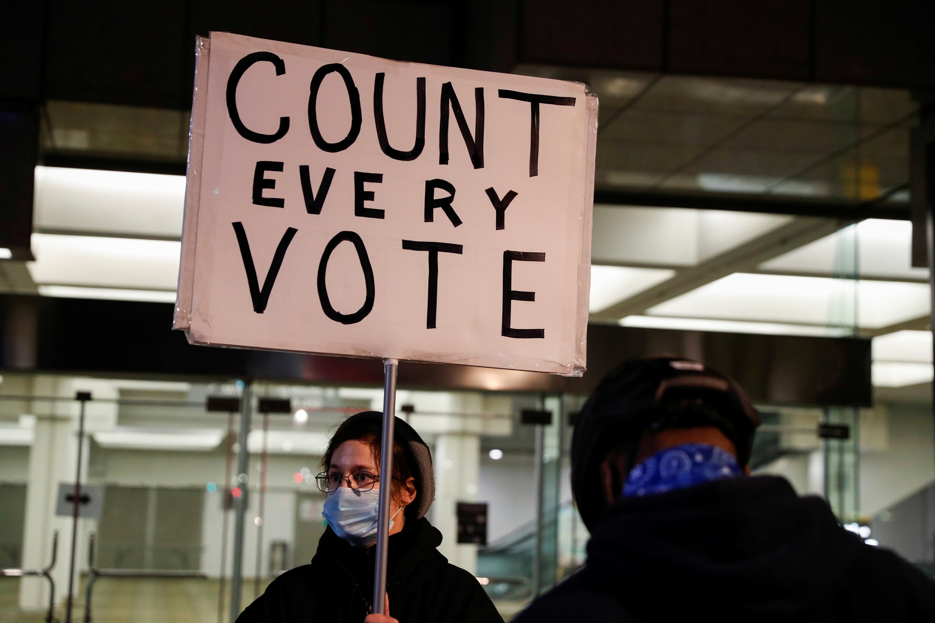 A person holding a count every vote sign