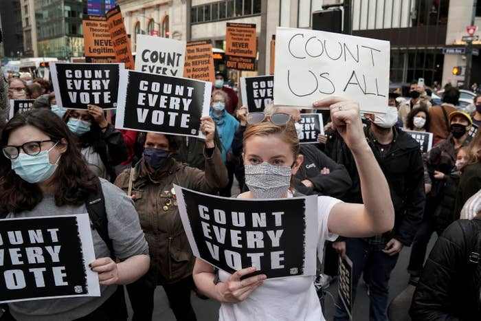 """People holding """"count us all"""" signs"""