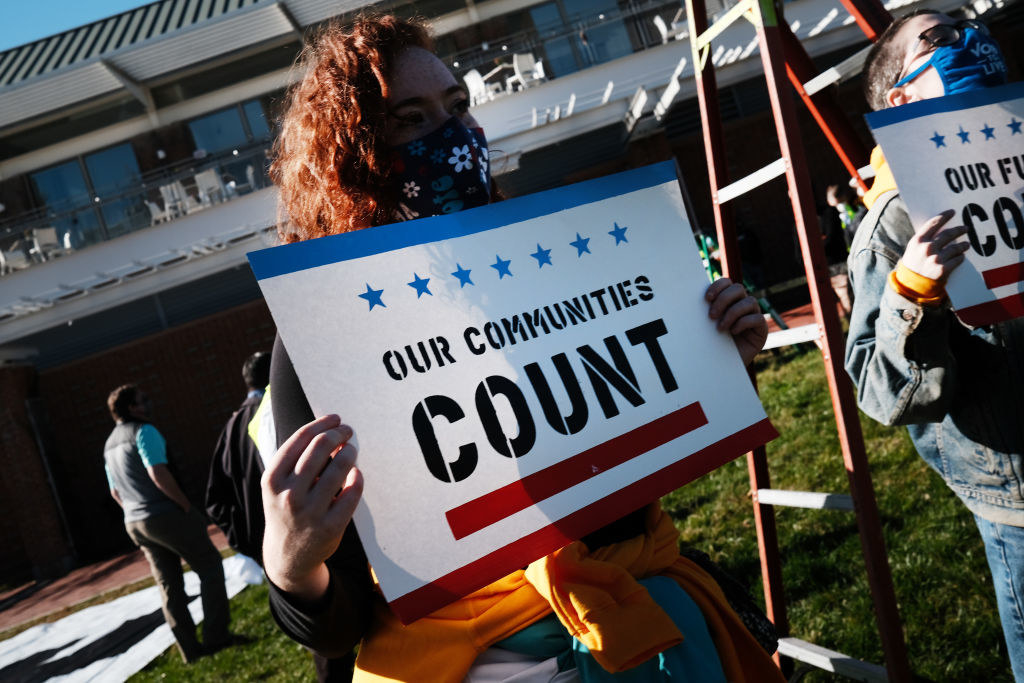 A woman with a our communities count sign
