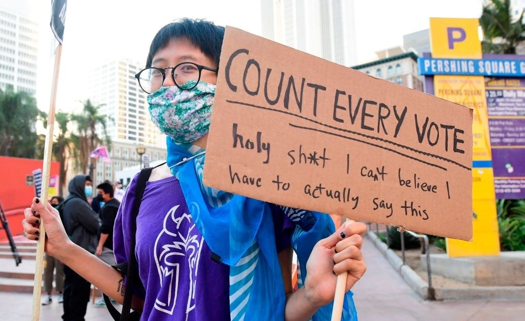 a person with a sign that says count every vote, holy shit i cant believe i have to actually say this