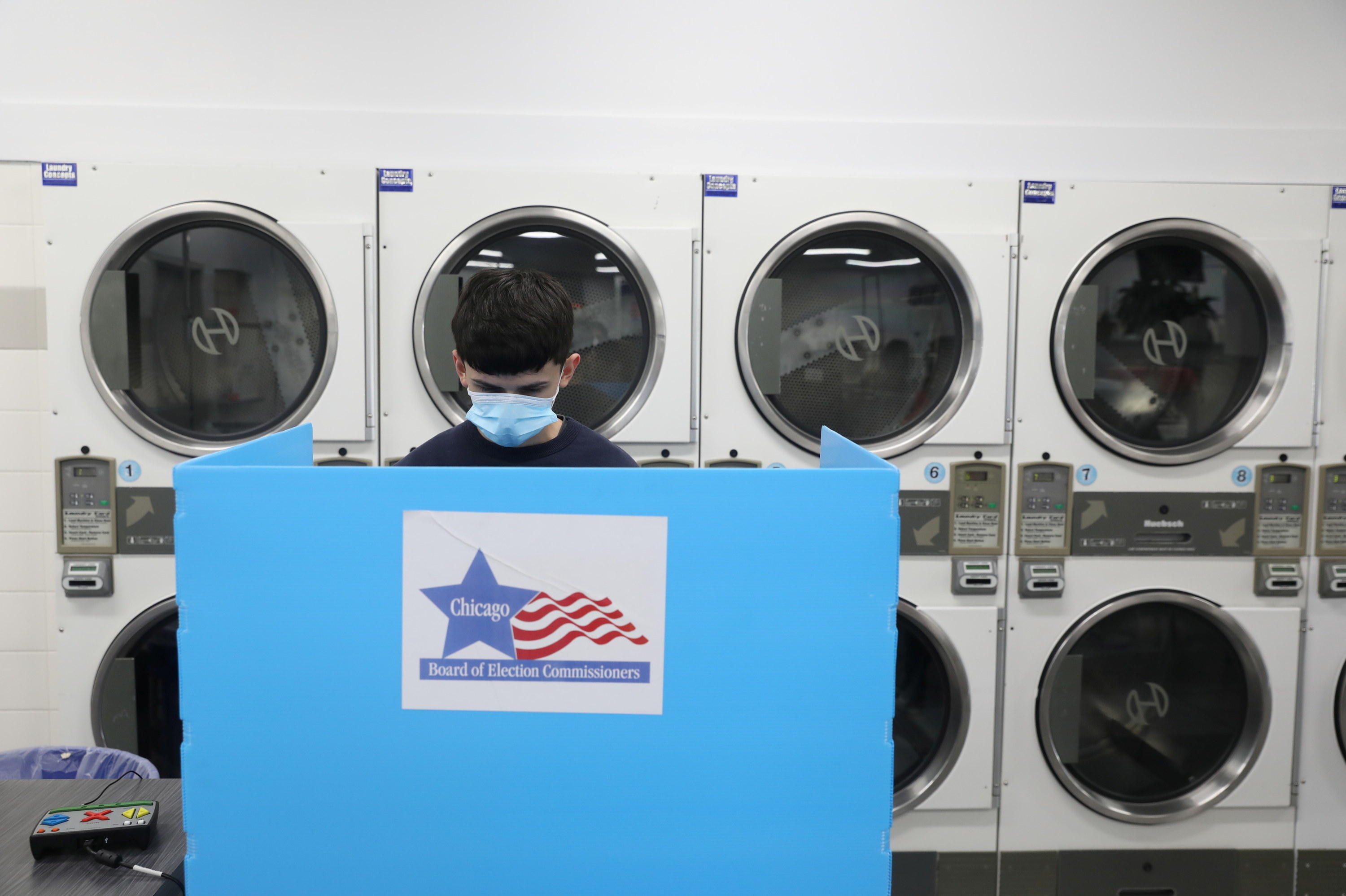 A man wearing a face mask stands behind a ballot booth at a polling place inside a laundromat