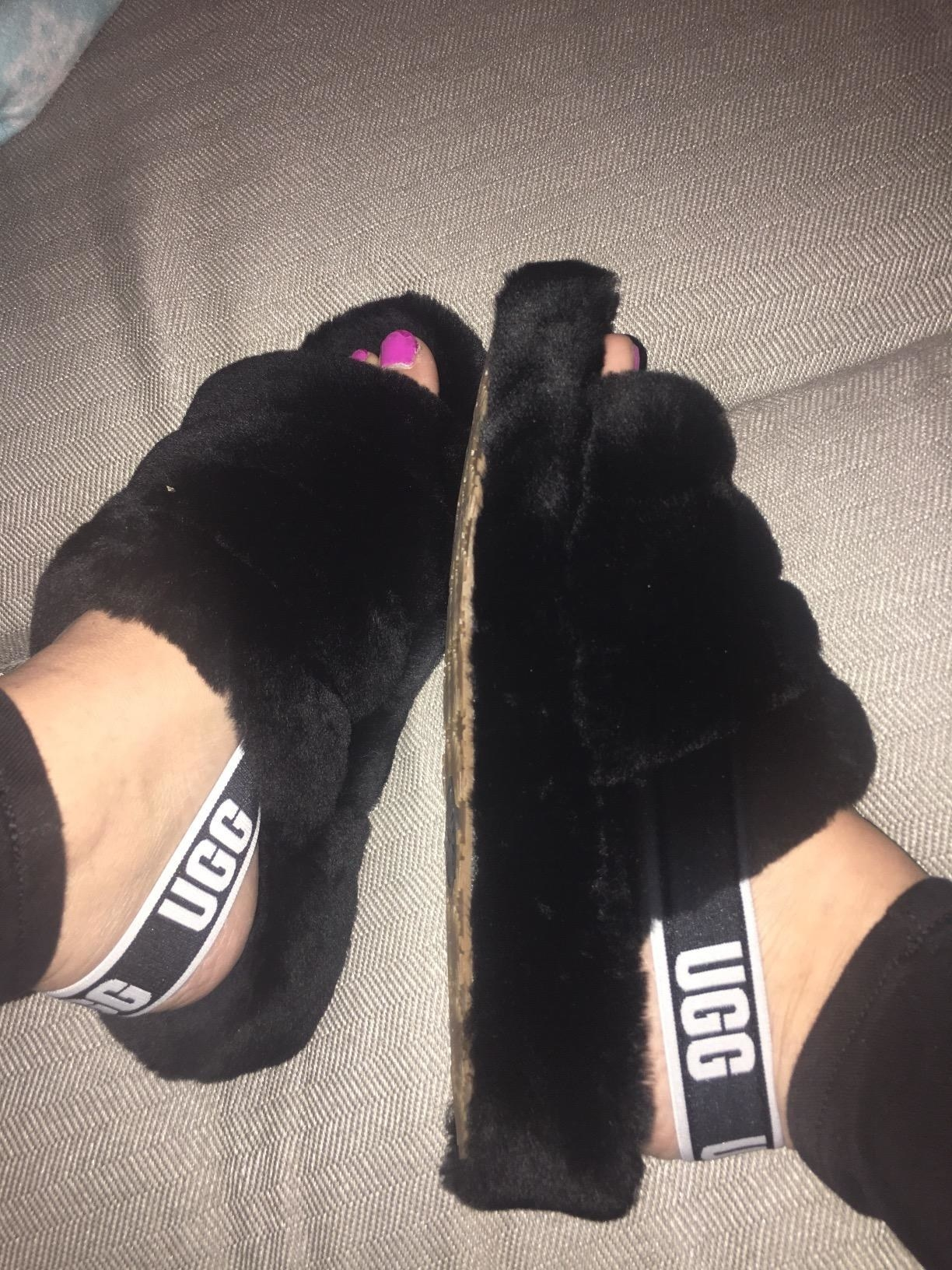 A reviewer wearing the slippers in black which are backless except for a back strap and are open-toed