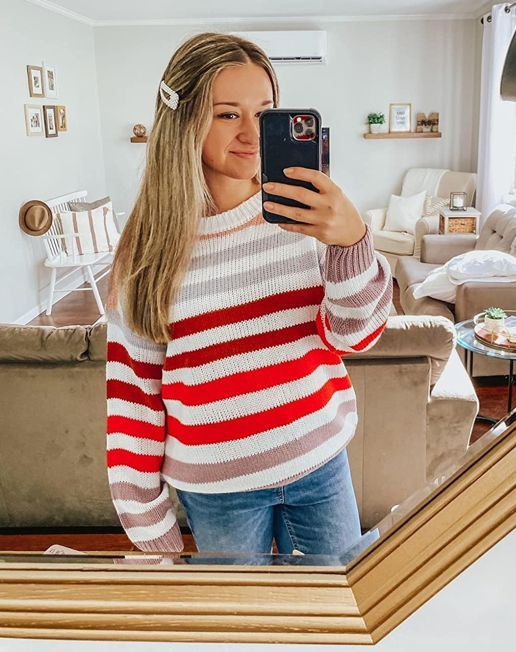 reviewer wearing a white, pink, red, and purple striped sweater