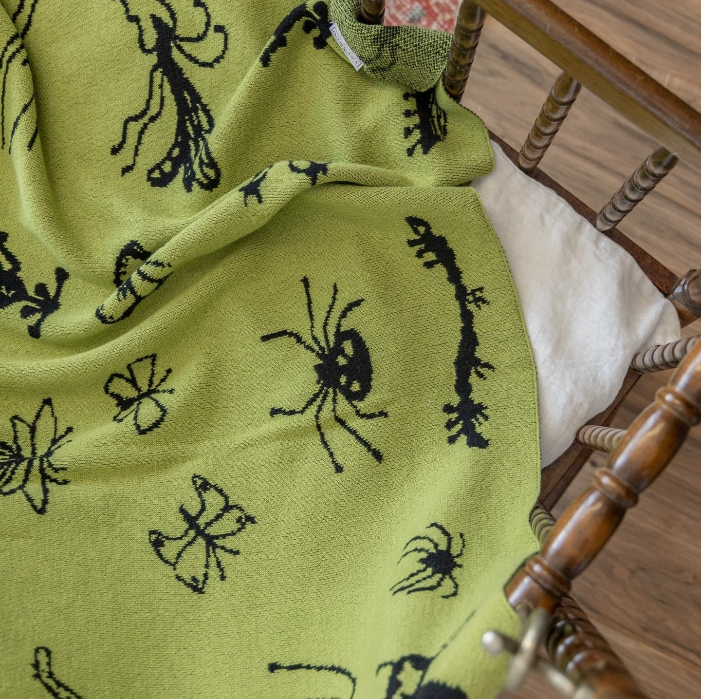 A lime green throw blanket with black bugs pattern