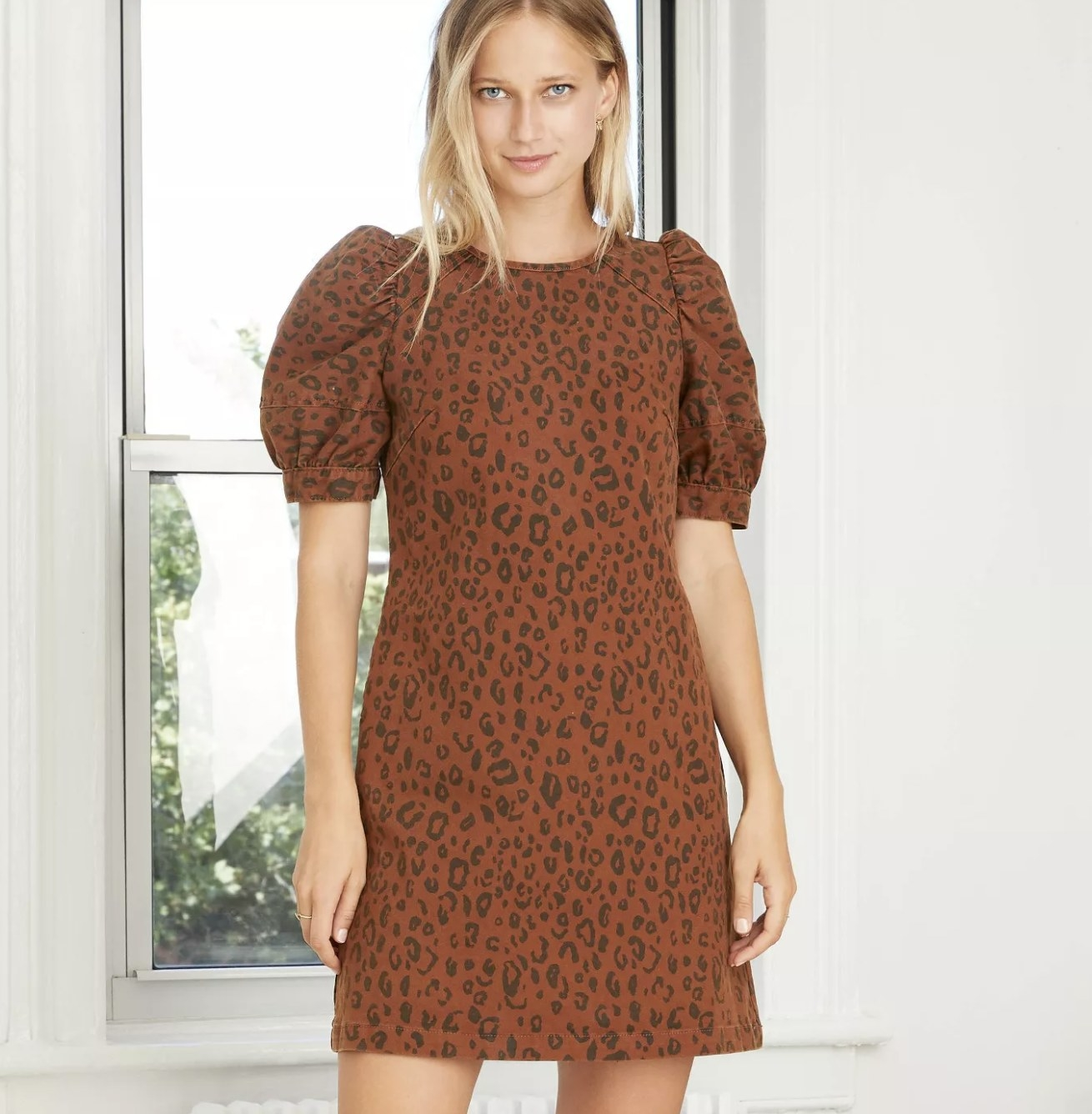 a brown structured denim dress with a chetah pattern and puff sleeves