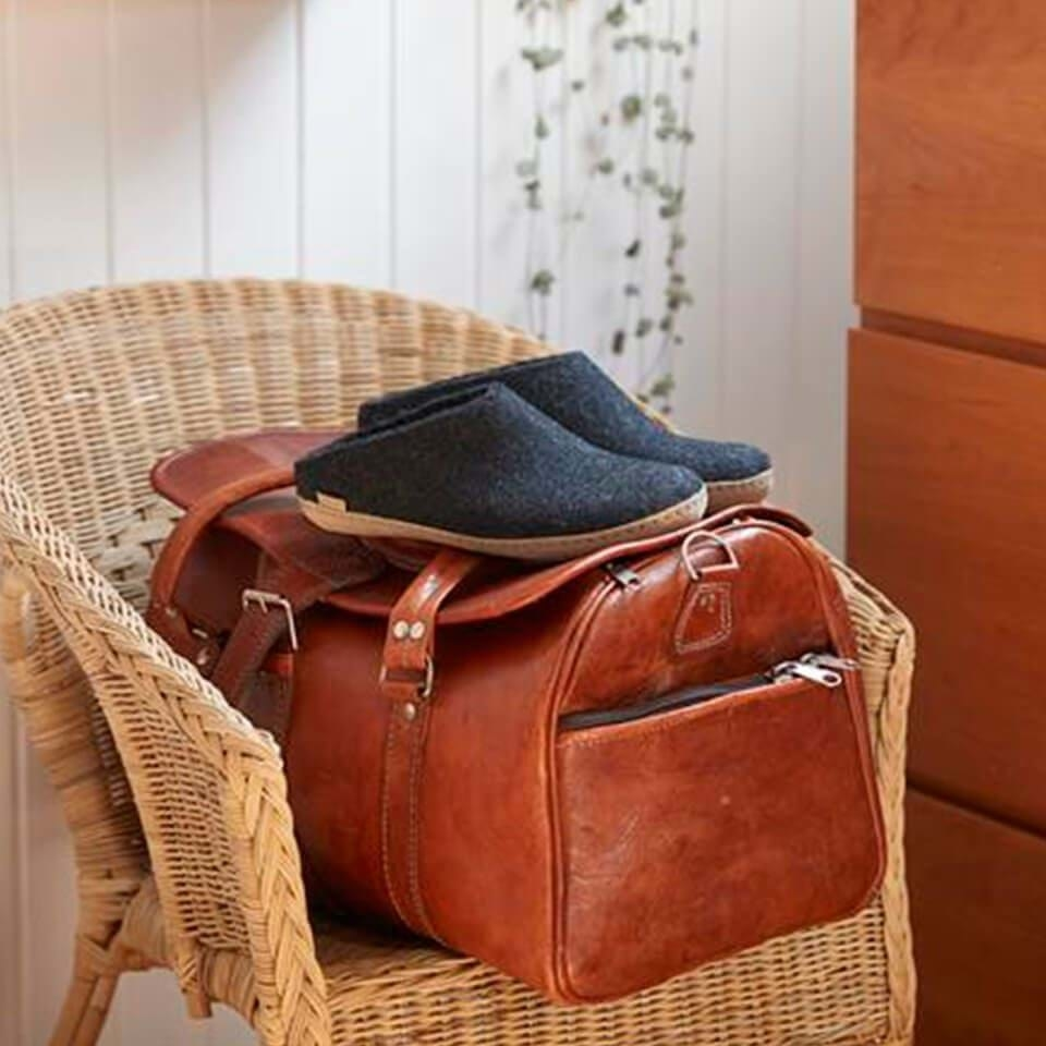 A pair of slip-on Glerups slippers set atop a leather bag
