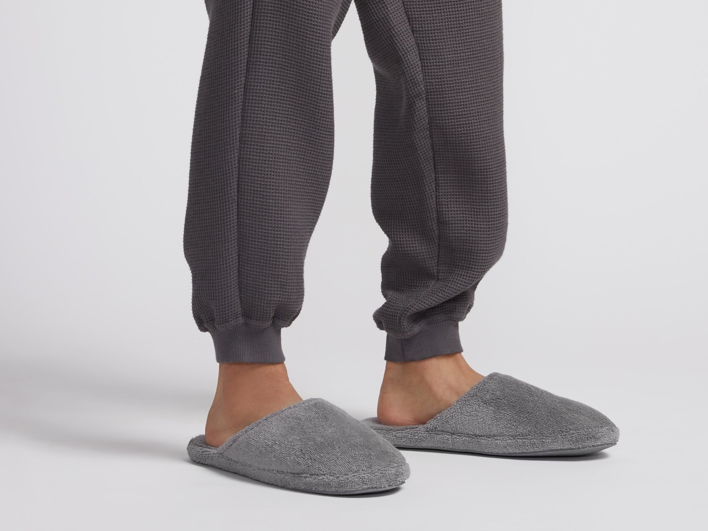 A model wearing joggers and gray closed-toed slippers