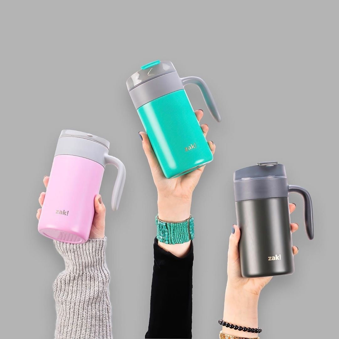 People holding the mugs in pink, teal, and gray