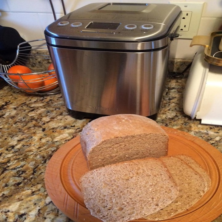 A reviewer photo of a bread machine on a counter with a plate of sliced bread