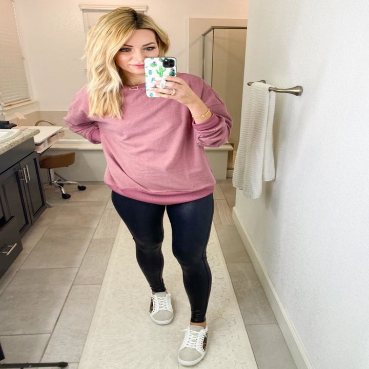 reviewer wearing the sweatshirt in pinkish-purple with leggings