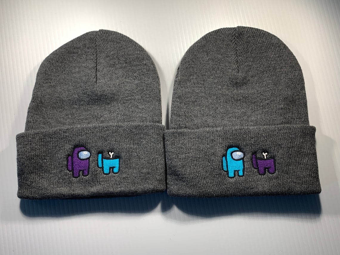 two beanies with an embroidered design of a crewmate character standing next to a dead crewmate character