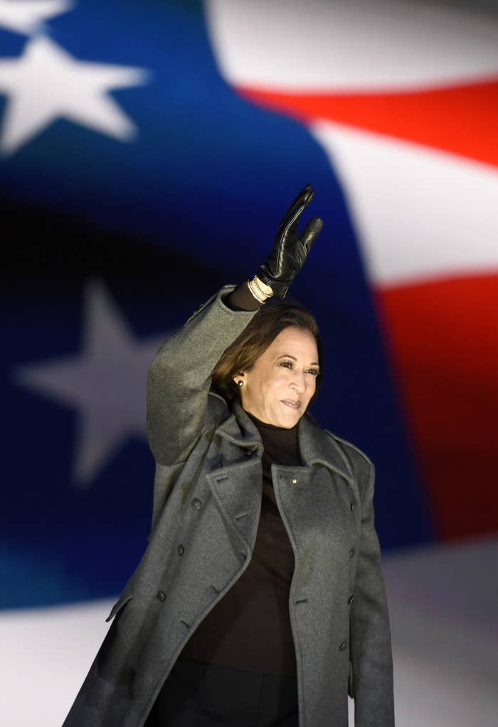 Kamala Harris waving in front of a flag.