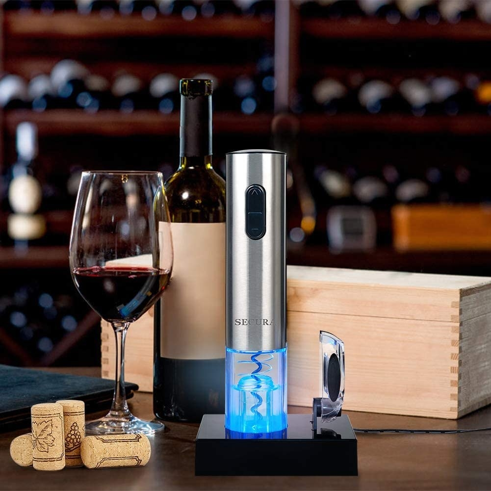 An electric wine opener on its docking station next to a glass of wine and a bottle