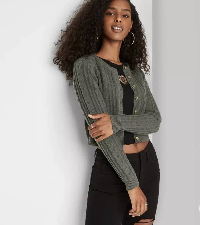 A model is wearing an olive green, cropped cardigan with buttons that is opened.
