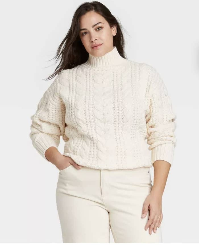 model wearing white cable knit sweater