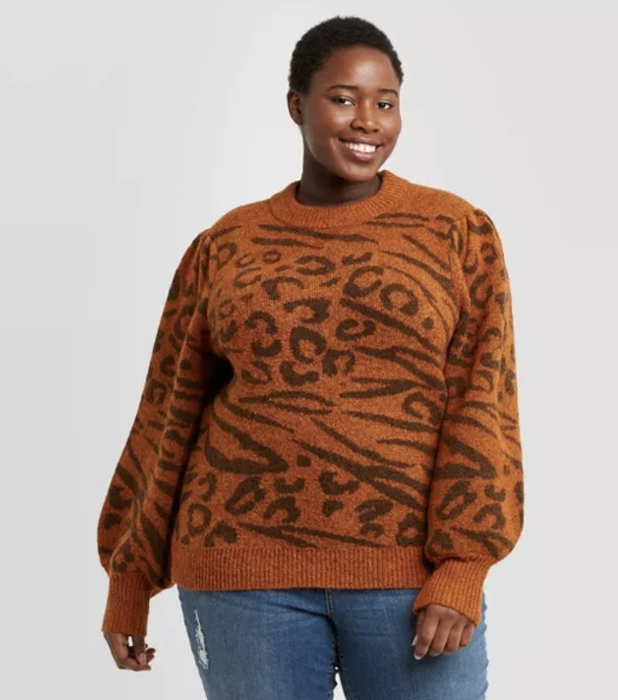 model wears a rust orange sweater with combined leopard and tiger print