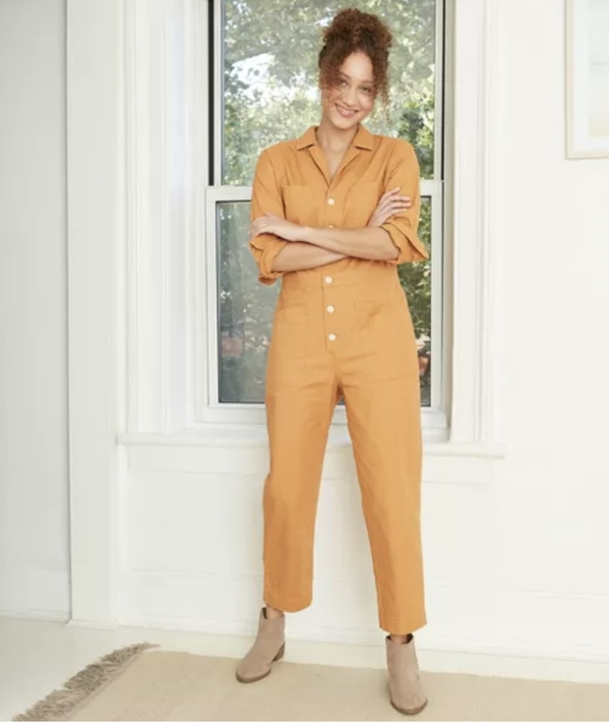 model wears yellow coverall while standing in front of a window