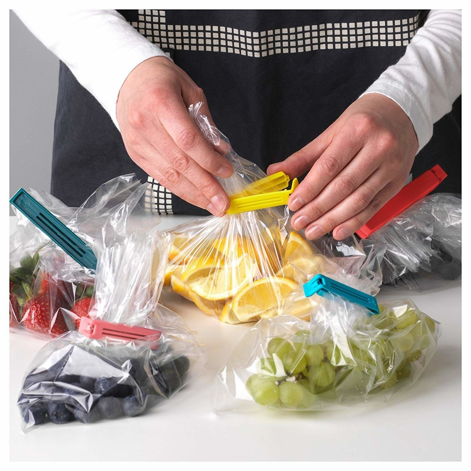 A person using baggie seals to pack plastic bags of food.