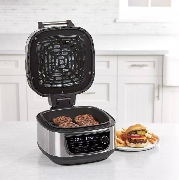 The air fryer with burger patties inside and next to a plate with a burger and fries on top