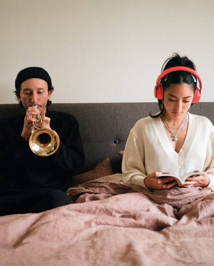 Person is sitting in bed with headphones in while the other person plays the trumpet next to them