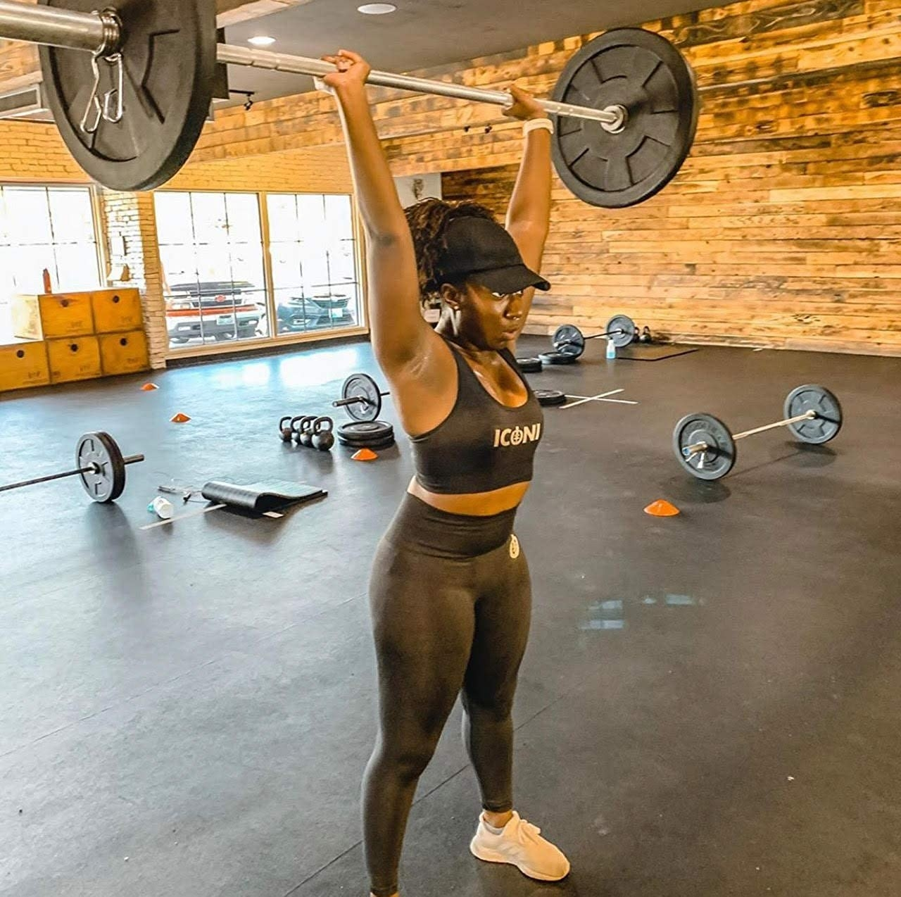 A model in the black leggings lifting a dumbell