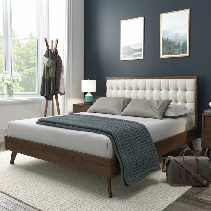 The bed with blue blanket draped over the edge