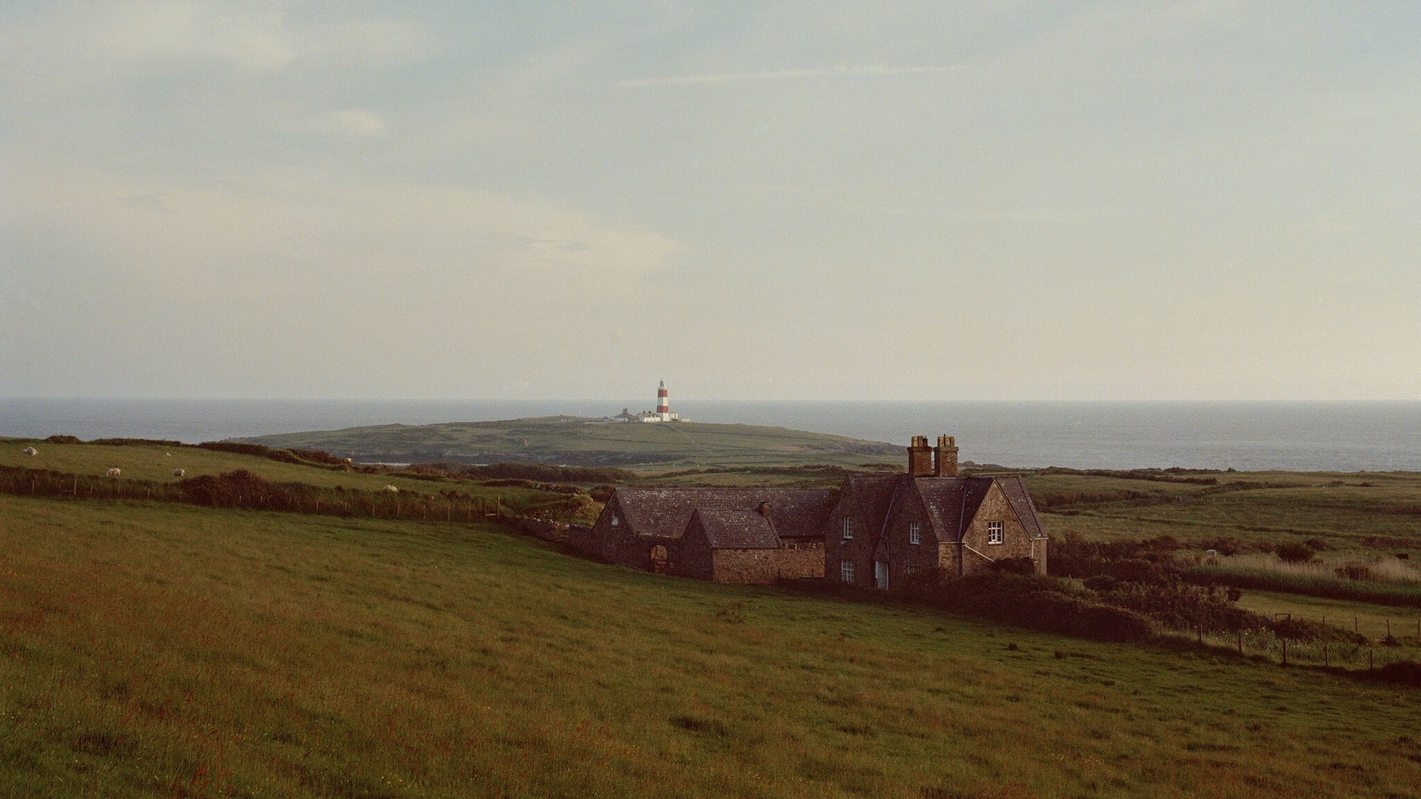 A lighthouse is visible in the distance; in the foreground, a home on an island